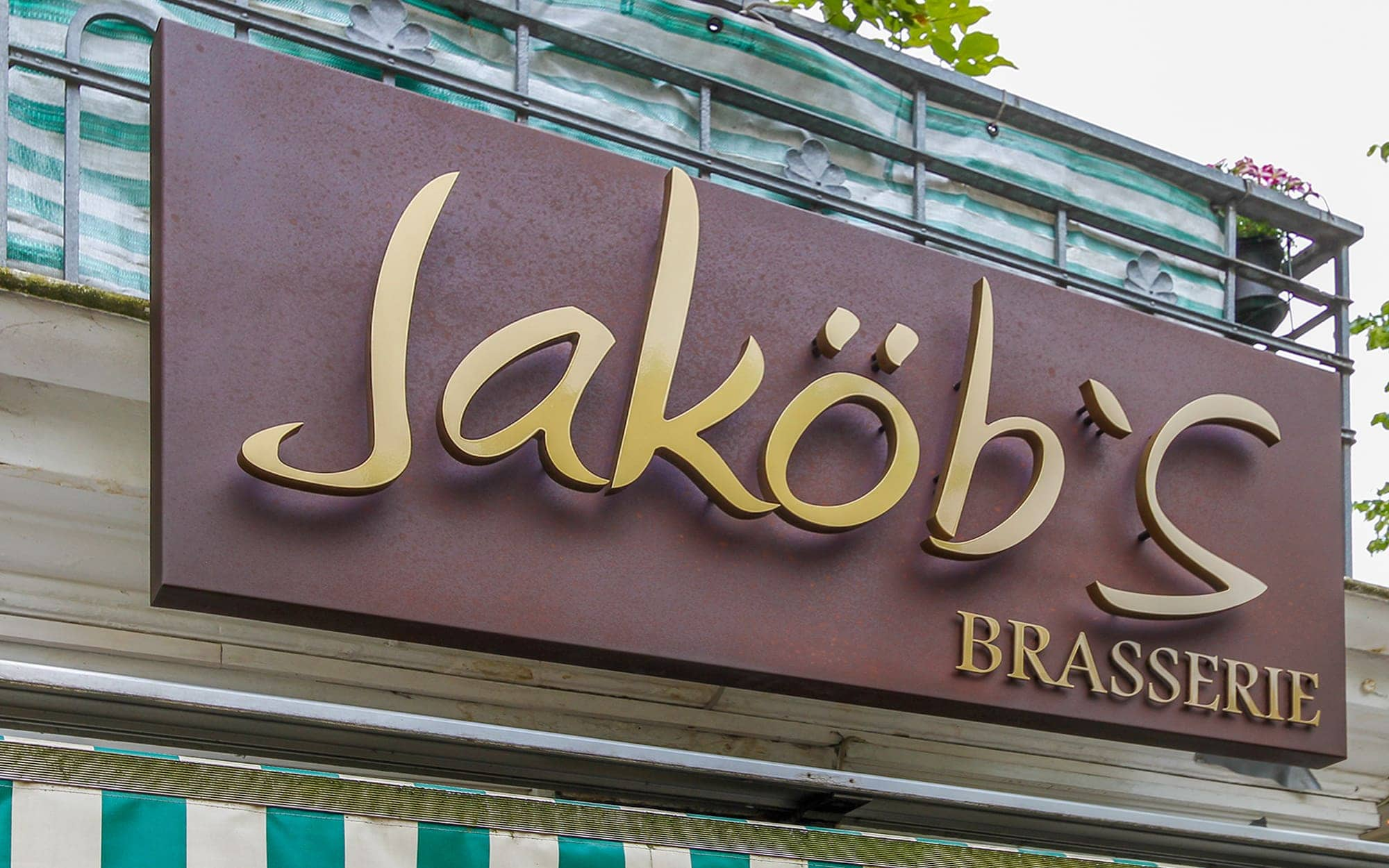Profilbuchstaben auf Abstand montiert auf ein abgekantetes Blech aus gerostetem Worten-Stahl. Werbung für eine Hamburger Brasserie