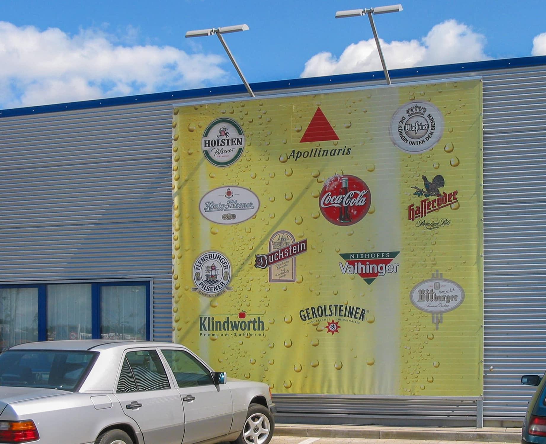 Digital bedruckte Planen als Werbefläche für eine Getränkemarkt. Angestrahlt mit LED-Strahlern