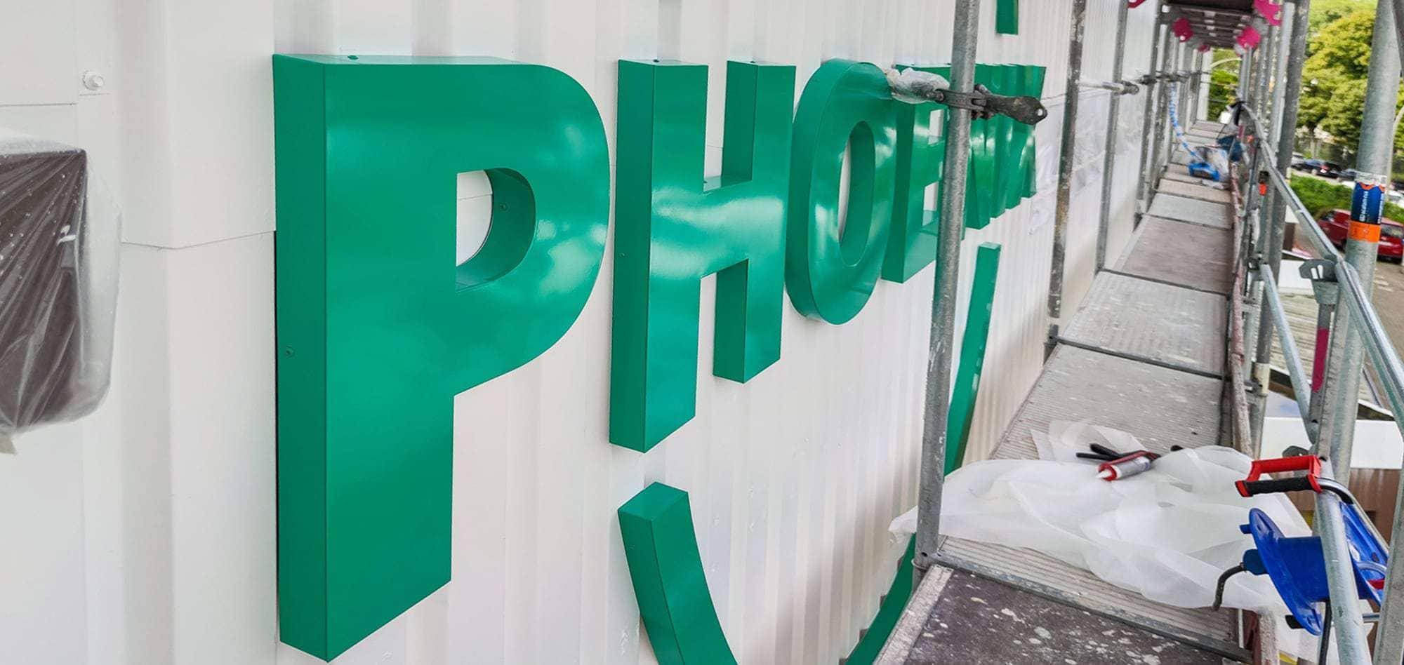 Foto einer 3D Buchstaben Anlage an einer Hausfassade. Dias Firmenlogo ist aus Aluminum gefertigt und lackiert