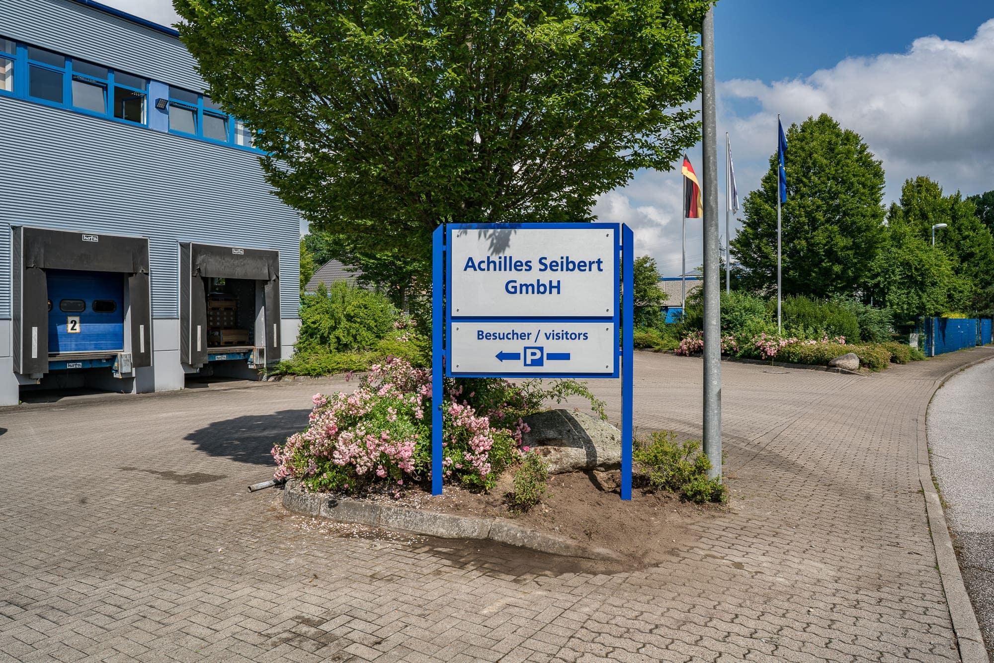 Das Foto zeigt ein Standschild gefertigt aus Aluminium und ESG-Glasscheiben. Das Firmenschild zeigt den Namen und einen Hinweis für die Kundenparkplätze.
